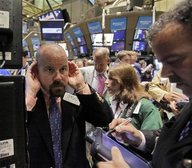 Specialist Daniel O'Donnell, left, cups his ears to hear a trader on the floor of the New York Stock Exchange Wednesday, June 10, 2009. (AP Photo/Richard Drew)